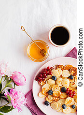 Tiny pancakes with berries, honey, flowers, coffee. Pancake cereal. The concept of Breakfast, food trends. Copy space.