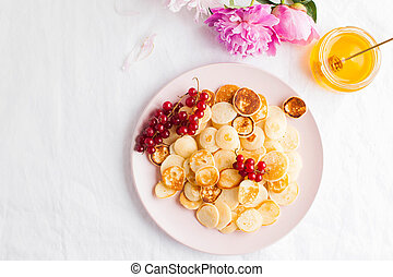 Tiny pancakes with berries, honey, flowers. Pancake cereal. The concept of Breakfast, food trends. Copy space.
