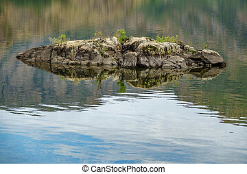 Tiny rock in the middle of a lake