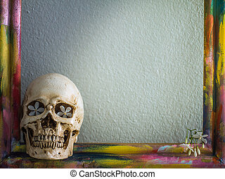 Tiny skulls with colorful wooden frame and flower