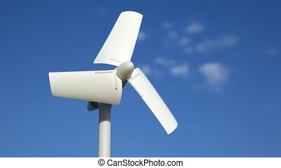 tiny wind driven generator rotating against sky - white tiny...