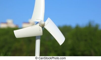 tiny wind driven generator rotating against nature - white...