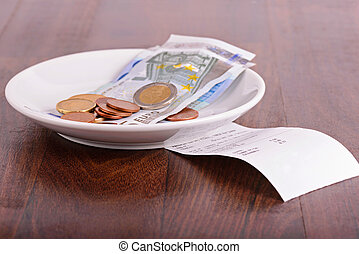 Tip on a restaurant table - Tip and bill on a wooden ...