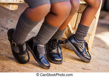 Tip toes - Two kids sitting on a bench waiting for the...