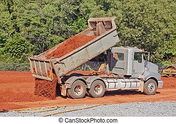 Tip truck dumping dirt on a construction site - A tip truck...
