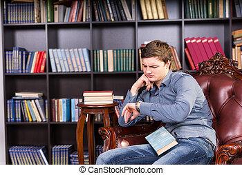 tipo, sentado, en, biblioteca, silla, el mirar, el suyo, reloj