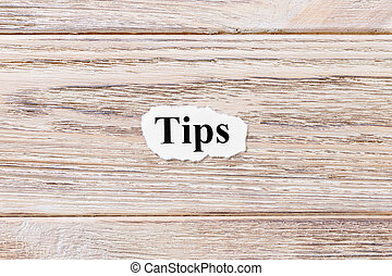 TIPS of the word on paper. concept. Words of TIPS on a wooden background