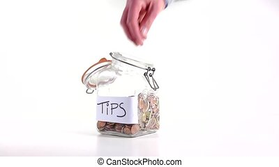 Tips - Person throwing cash at a tip jar