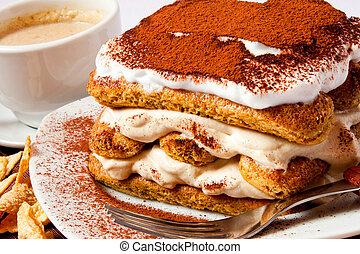 Delicious italian dessert with wafers, mascarpone and cream and hot cappuccino in the background