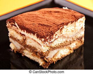 Tiramisu cake in a black plate, close up