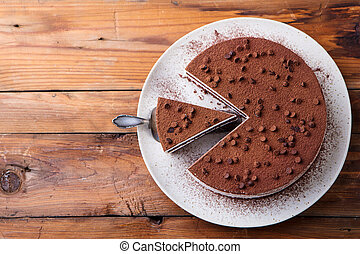 Tiramisu cake with chocolate decotaion on a plate. Wooden background. Copy space. Top view.