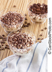 Tiramisu dessert in a glass cup on wooden table