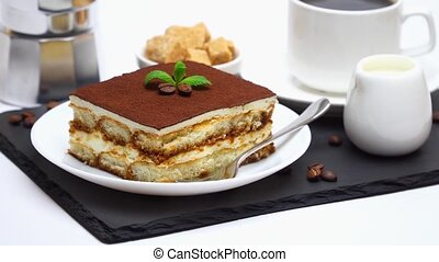 Tiramisu dessert portion, mocha coffee maker, milk or cream...