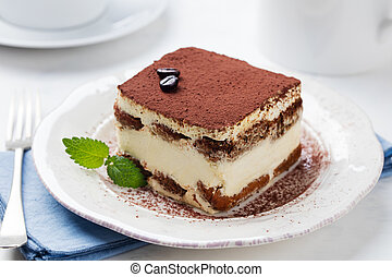 Tiramisu, traditional Italian dessert on a white plate