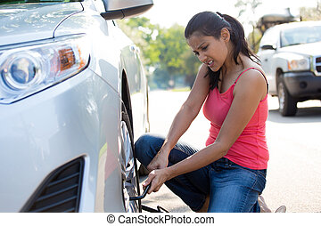 Tire change - Closeup portrait, young woman in pink tanktop ...