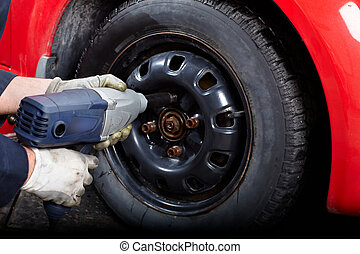 Tire changing - Mechanic changing wheel on car with impact...