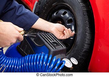 Tire pressure - Mechanic inspecting the tire pressure in...