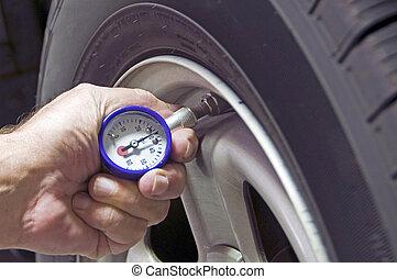 Tire Pressure - Mechanic checking tire pressure for...