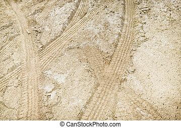 Tire tread marks in dirt.