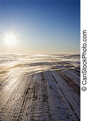 Tire tracks on icy road. - Ice covered road with tire...