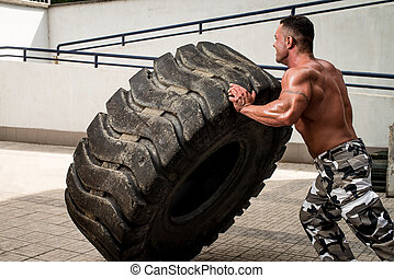 Muscular Man with Truck Tire doing crossfit style workout turning tire over