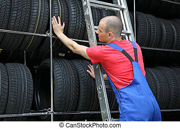 Tire Workshop - A motivated worker in a tire workshop ...