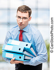 Tired accountant with a bunch of documents in the office