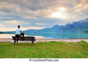 Tired adult man in blue shirt sit on old wooden bench at mountain lake coast