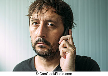 Tired adult man talking on mobile phone
