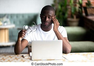 Tired African American man taking off glasses, feel eye strain