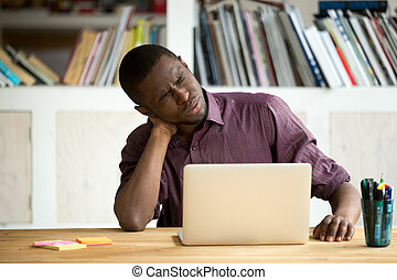 Tired African American office worker suffering from neck pain