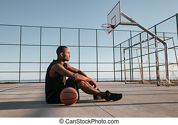 Tired african sports man sitting with basketball at the playground