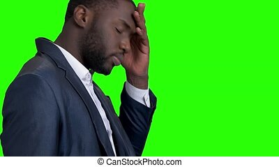 Tired afro american businessman on green screen.