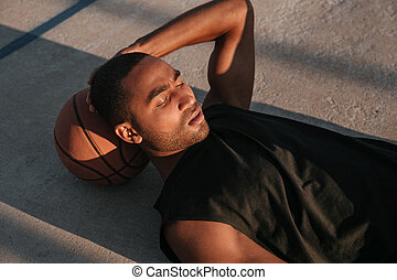 Tired afro american sports man resting on a basketball