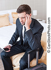 Tired after long business trip. Depressed young businessman in formalwear holding mobile phone and touching head with hand while sitting on the bed in hotel room