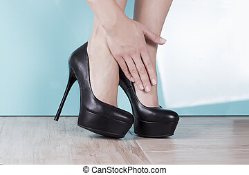 Tired and aching female feet after walking in high-heeled shoes
