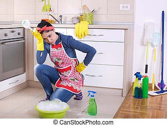 Tired and depressed cleaning lady in kitchen - Unhappy young...