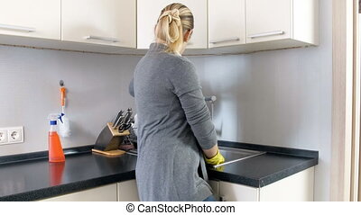 Tired and exhausted housewife standing on kitchen after washing dishes