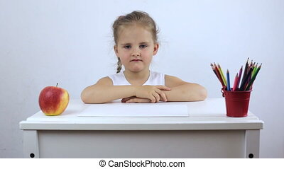 Tired and frustrated small girl sitting at a school desk