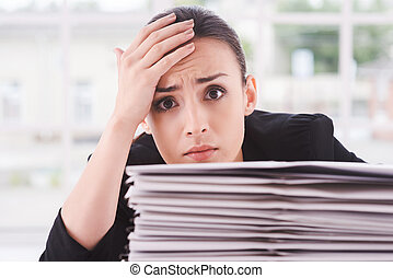 Tired and overworked. Depressed young woman in suit looking out of the stack of documents laying on the table and touching her forehead with hand