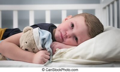 Tired and sad child due to problems in family is sad lying on bed alone hugging his best friend teddy bear. Problems of childhood depression, bad attitude in family, strict portrait of little boy.