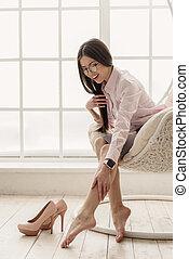 Tired asian woman feeling pain in legs