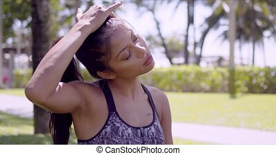 Tired Asian woman rubbing head with closed eyes in park
