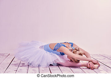 Tired ballet dancer lying on the wooden floor