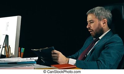 Tired bearded businessman yawning at his desk. Black background.