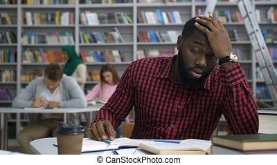 Overworked handsome african american student studying difficult university assignment, covering his forehead with arms, feeling fatigue and exhaustion during learning in academic library.