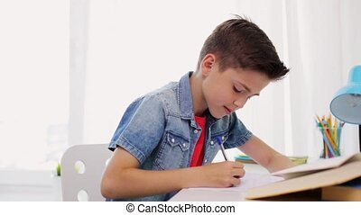 tired boy with book writing to notebook at home - education,...