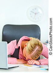 Tired business woman sleeping on office desk