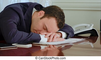 Tired businessman awakened by phone call and answer - Close...