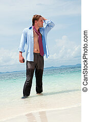 Tired businessman on the beach